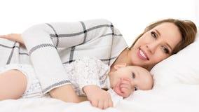 Giovane madre sorridente felice e suo il figlio del bambino che si trovano insieme su un letto Ritratto del bambino neonato e del Fotografia Stock