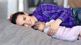 Giovane madre sorridente preoccupantesi che abbraccia bambino addormentato che esamina il colpo di medium della macchina fotograf stock footage
