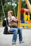 Giovane madre su un'oscillazione con il bambino immagini stock libere da diritti
