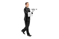 Giovane maggiordomo con il legame di arco che trasporta un cassetto Fotografia Stock