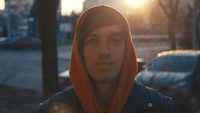 Giovane in maglia con cappuccio che sorride e che esamina macchina fotografica il tramonto Ritratto dell'uomo bello felice in via stock footage