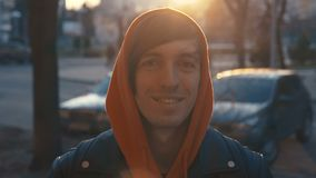 Giovane in maglia con cappuccio che sorride e che esamina macchina fotografica il tramonto Ritratto dell'uomo bello felice in via video d archivio