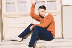 Giovane in maglione che si siede sui punti davanti alla casa e al posi Fotografia Stock