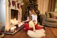 Giovane mamma che accende le candele con il suo piccolo figlio immagini stock libere da diritti