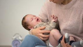 Giovane mamma che alimenta poco figlio del bambino dalla bottiglia, alimentazione artificiale di formula infantile stock footage