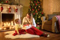 Giovane mamma che dà a suo figlio un presente del nuovo anno immagini stock