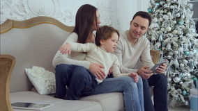 Giovane mamma che gioca con il suo piccolo figlio energetico mentre papà che per mezzo della compressa stock footage