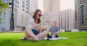 Giovane mamma con fare da baby-sitter sull'erba nel parco che mangia pranzo archivi video