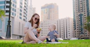 Giovane mamma con fare da baby-sitter sull'erba nel parco che mangia pranzo video d archivio