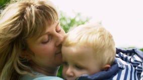 Giovane mamma della famiglia felice e bambino sveglio che baciano e che abbracciano nel movimento lento del parco video d archivio