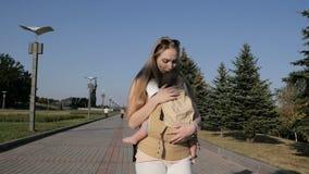 Giovane mamma felice con la neonata in ergo zaino che cammina nel parco archivi video
