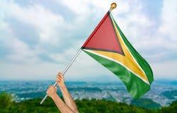 Giovane man& x27; la s passa fiero l'ondeggiamento della bandiera nazionale della Guyana nel cielo, rappresentazione della parte  Fotografia Stock Libera da Diritti