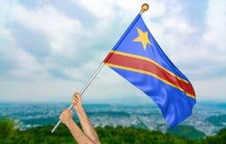 Giovane man& x27; la s passa fiero l'ondeggiamento della bandiera nazionale del Dott Congo nel cielo, rappresentazione della part Immagine Stock