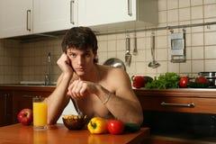 Giovane mangiatore di uomini muscolare la sua prima colazione immagine stock libera da diritti