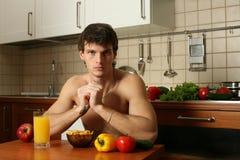 Giovane mangiatore di uomini muscolare la sua prima colazione fotografie stock