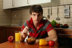 Giovane mangiatore di uomini sexy la sua prima colazione fotografia stock libera da diritti