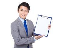 Giovane manifestazione dell'uomo d'affari con la pagina in bianco della lavagna per appunti Fotografie Stock