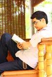 Giovane manuale asiatico di seduta e della lettura dell'allievo Immagine Stock Libera da Diritti