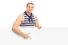 Giovane marinaio che indica su un'insegna in bianco Fotografia Stock