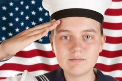 Giovane marinaio che saluta davanti alla bandierina degli Stati Uniti Immagini Stock Libere da Diritti