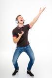 Giovane maschio allegro che ascolta la musica, il canto ed il dancing fotografia stock