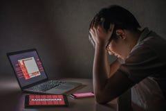 Giovane maschio asiatico frustrato tramite l'attacco del ransomware di WannaCry fotografia stock libera da diritti