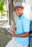 Giovane maschio attraente facendo uso del pc della compressa immagini stock