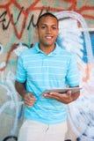 Giovane maschio attraente facendo uso del pc della compressa fotografie stock