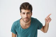 Giovane maschio caucasico allegro che porta maglietta blu con taglio di capelli alla moda che indica il suo dito indice lateralme Fotografia Stock Libera da Diritti