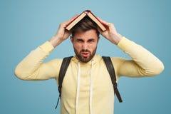 Giovane maschio con il libro che sembra infelice Immagine Stock Libera da Diritti