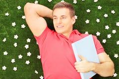 Giovane maschio con il libro che si trova su un'erba con le margherite Fotografie Stock