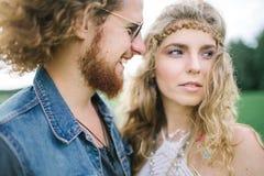 Giovane maschio di hippy con la barba che abbraccia femmina riccia all'aperto fotografia stock libera da diritti