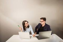 Giovane maschio e soci commerciali femminili che si siedono dietro un monitor del computer e che pensano a qualcosa fotografia stock