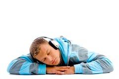 Giovane maschio felice con le cuffie ed i pollici in su Fotografia Stock