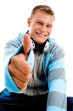 Giovane maschio felice con le cuffie ed i pollici in su Immagine Stock
