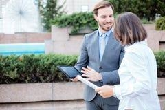 Giovane maschio felice e gente di affari femminile che parlano davanti ad un edificio per uffici, avendo una riunione e una discu fotografie stock libere da diritti