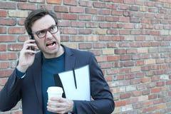 Giovane maschio infastidito sul telefono con spazio per la copia Fotografie Stock Libere da Diritti