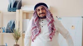 Giovane maschio musulmano bello in abbigliamento islamico tradizionale che sta davanti al grafico finanziario dipinto sul bordo b archivi video