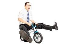 Giovane maschio nerd con il legame che guida una piccola bicicletta immagine stock