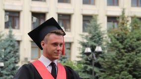 Giovane maschio sicuro in cappuccio di graduazione che posa per la macchina fotografica vicino all'accademia, studente stock footage