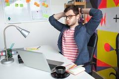 Giovane maschio sollecitato in ufficio moderno con il computer portatile Immagini Stock