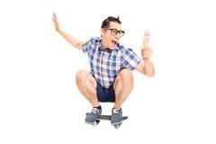 Giovane maschio sorridente su un bordo del pattino con il gelato fotografia stock
