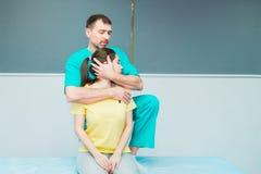 Giovane massaggio di ricezione femminile dal chiropratico del terapista A che allunga il suo collo paziente del ` s in ufficio me Immagine Stock