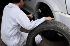 Giovane meccanico professionista in chiave e gomma della tenuta dell'uniforme di bianco ai precedenti del garage di riparazione fotografie stock