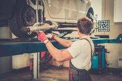 Giovane meccanico in un'officina dell'automobile Immagine Stock