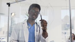 Giovane medico africano scrive a bordo di una certa formula medica nell'auditorium nell'ospedale Medico afroamericano stock footage