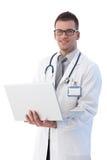 Giovane medico allegro con sorridere del computer portatile Immagini Stock