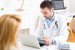Giovane medico attraente che ascolta il suo paziente Fotografia Stock Libera da Diritti