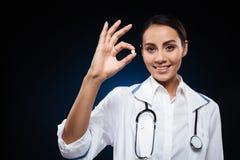 Giovane medico attraente di signora che mostra pillola e sorridere fotografie stock libere da diritti