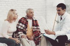 Giovane medico in cappotto che visita le vecchie coppie a casa immagine stock
